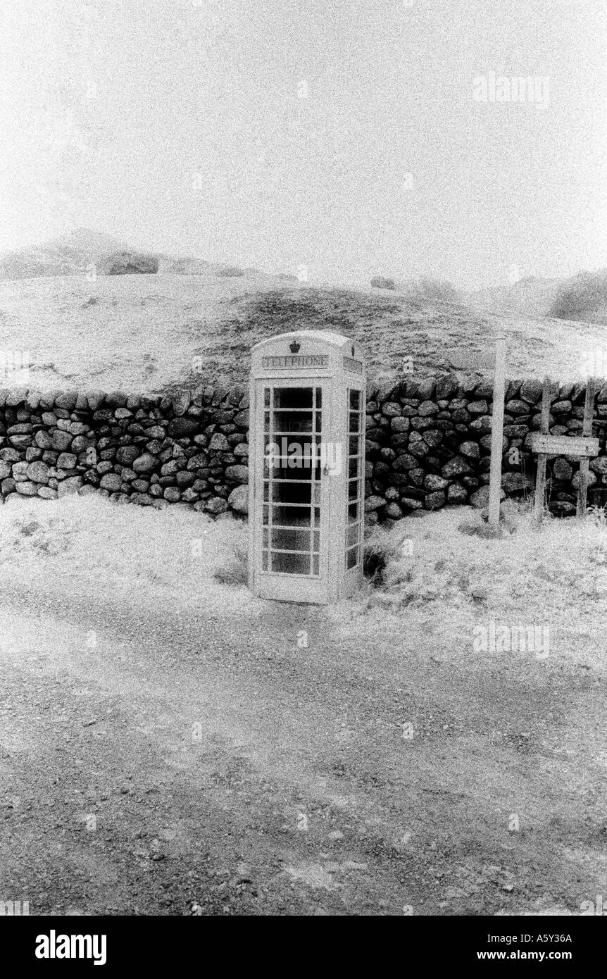 phone telephone booth box infrared weird history wall stone lonely - Stock Image