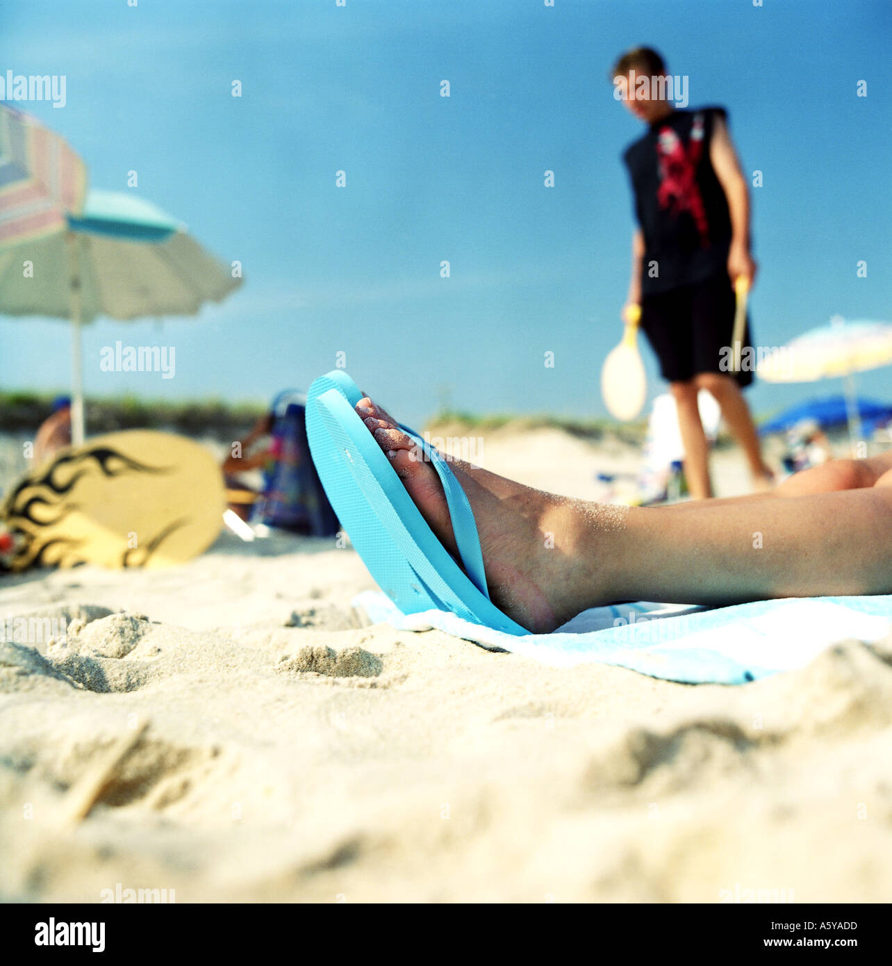 Beach Scene In the background a teenage boy in the front one sees woman s feet in flip flops - Stock Image