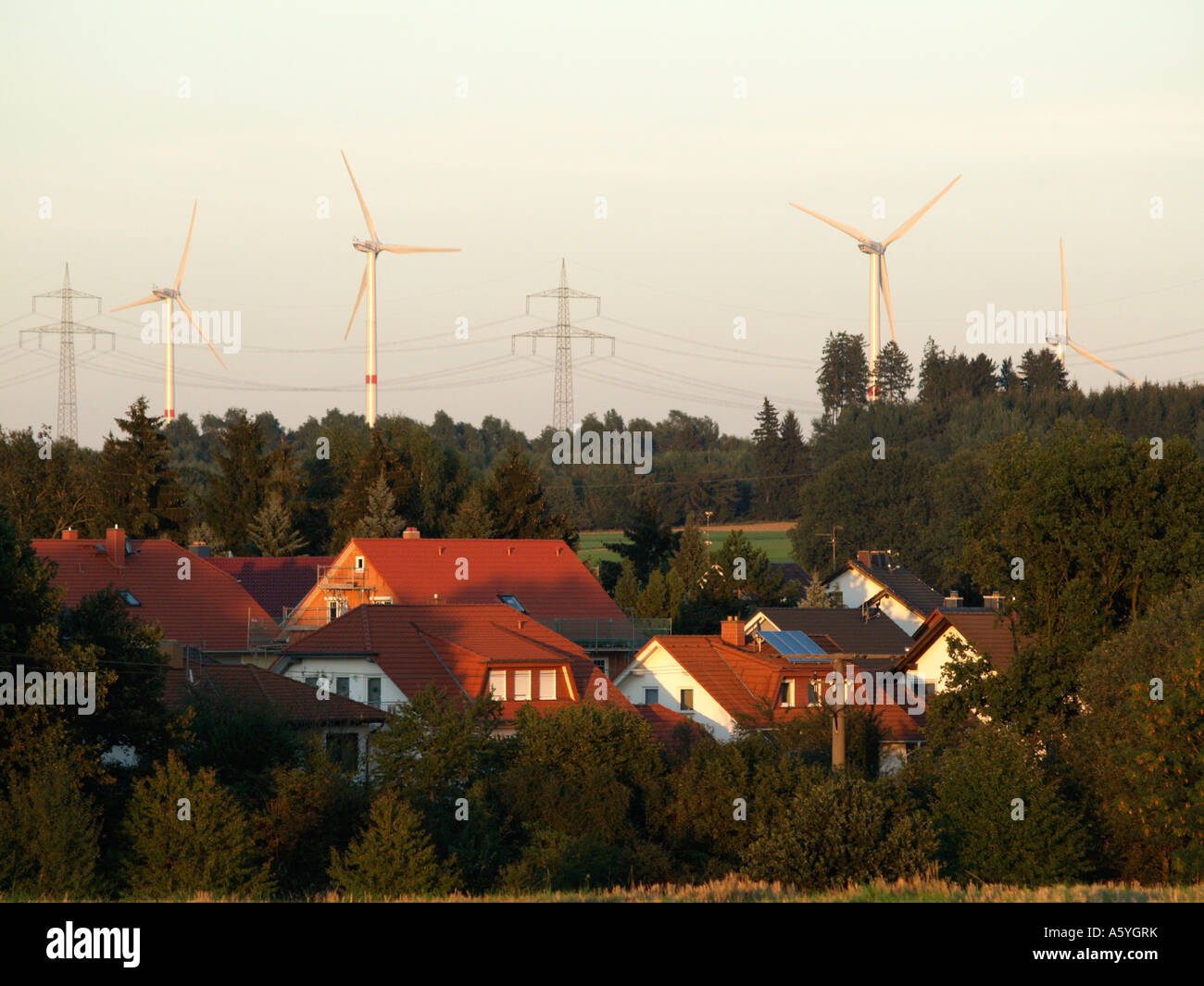 wind power station wind wheel behind a village in country landscape of low mountain range solar cells modules - Stock Image