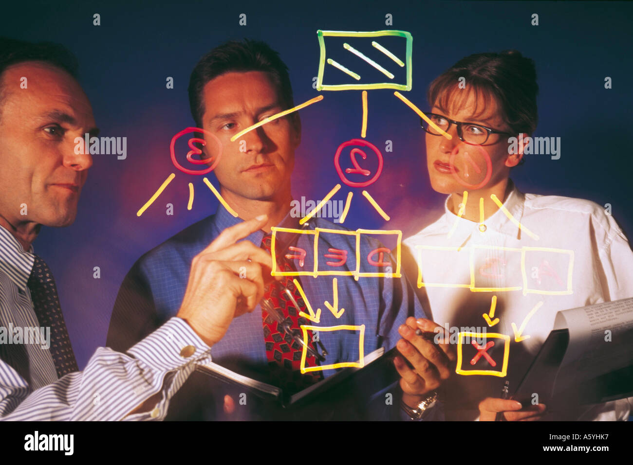 Three business executives discussing a hierarchy graph - Stock Image