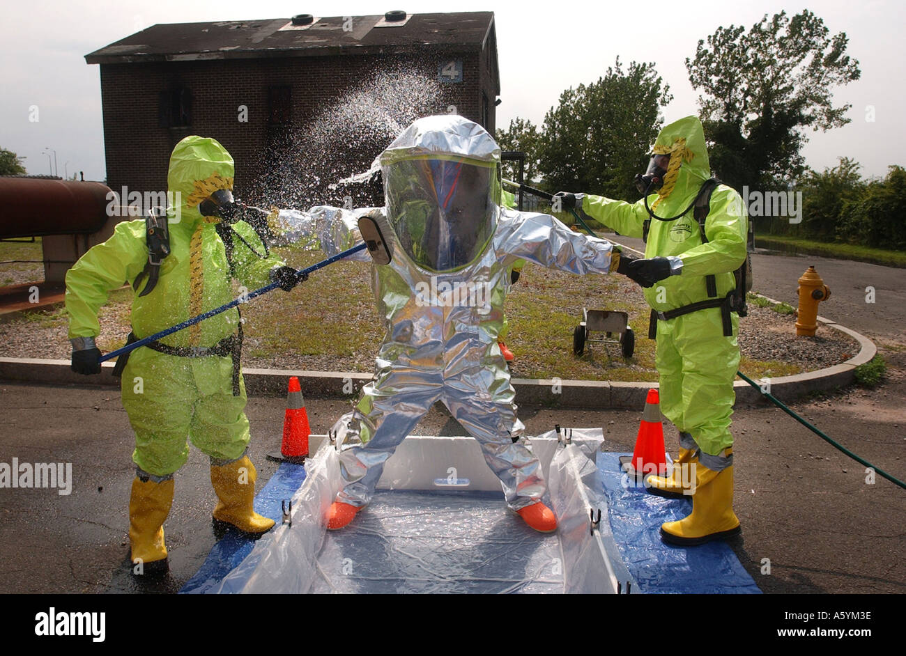Emergency workers cleaning each other off in chemical suits after bio hazard training drill - Stock Image