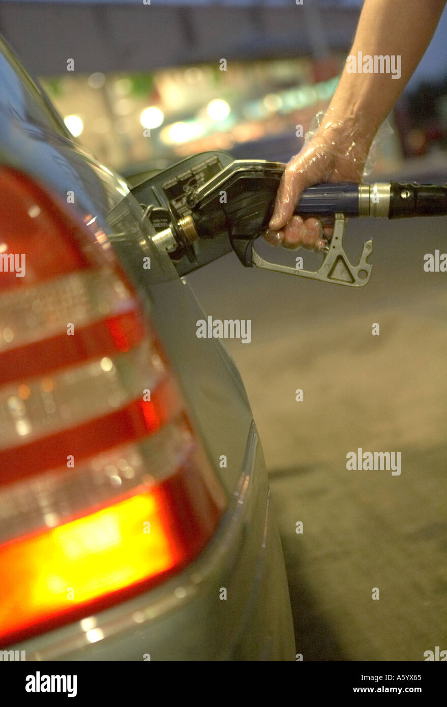 MALE HAND WEARING TRANSPARENT PLASTIC GLOVE WHILE FILLING CAR FUEL TANK WITH DIESEL - Stock Image