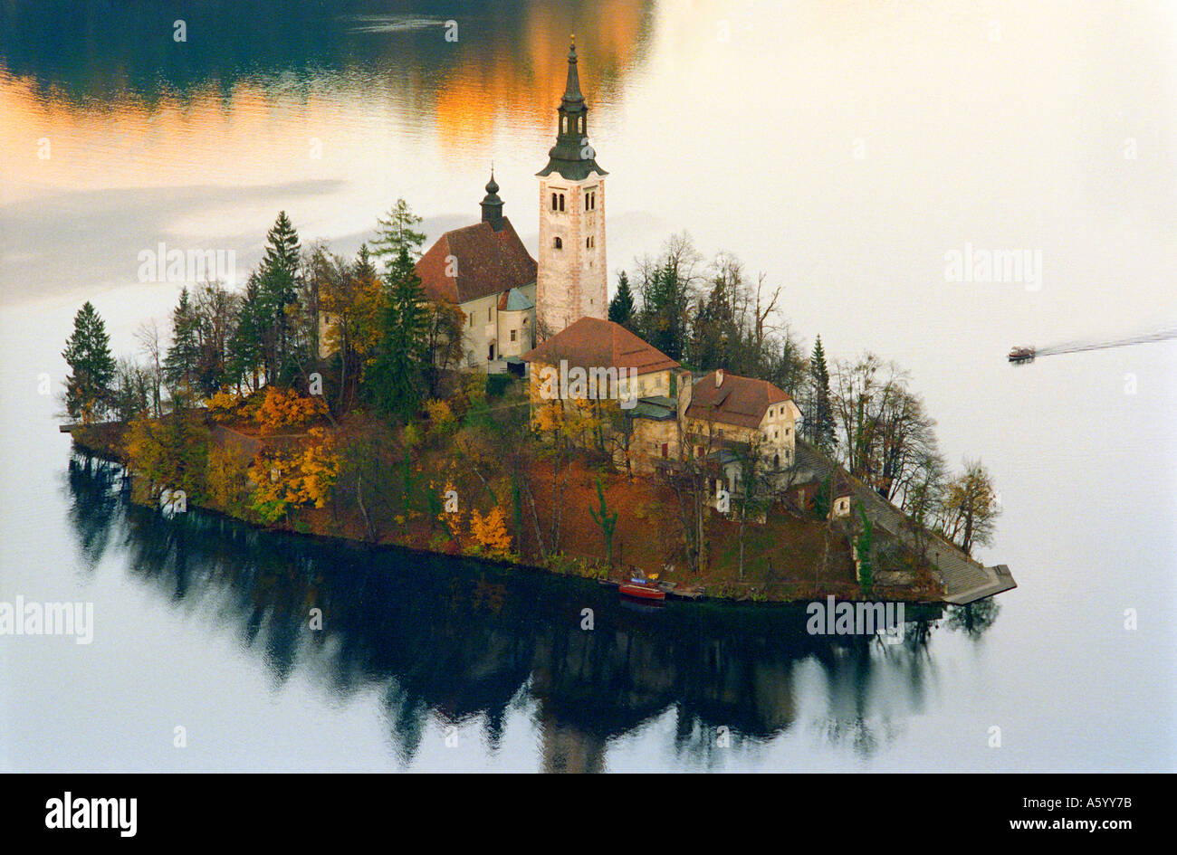 LAKE BLED ISLAND AUTUMN The church island and tourist tour boat at Lake Bled with autumnal colour Slovenia - Stock Image