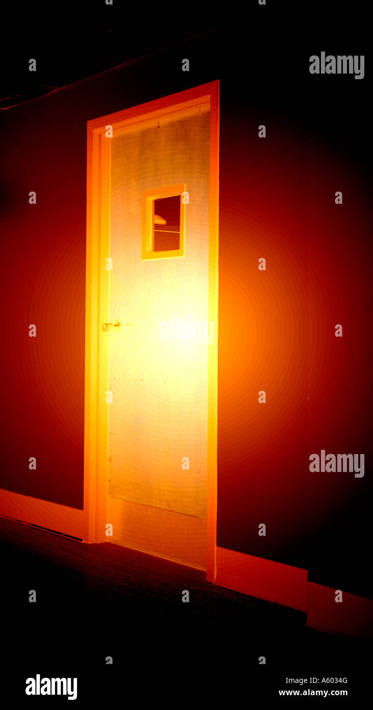 mysterious looking door glowing in darkness - Stock Image