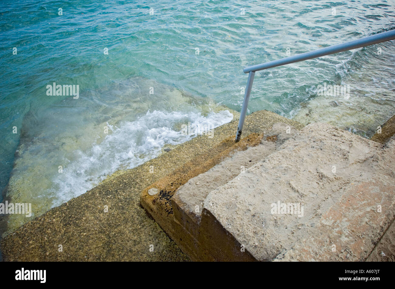 stairs to water cement concrete stairway steps wet - Stock Image