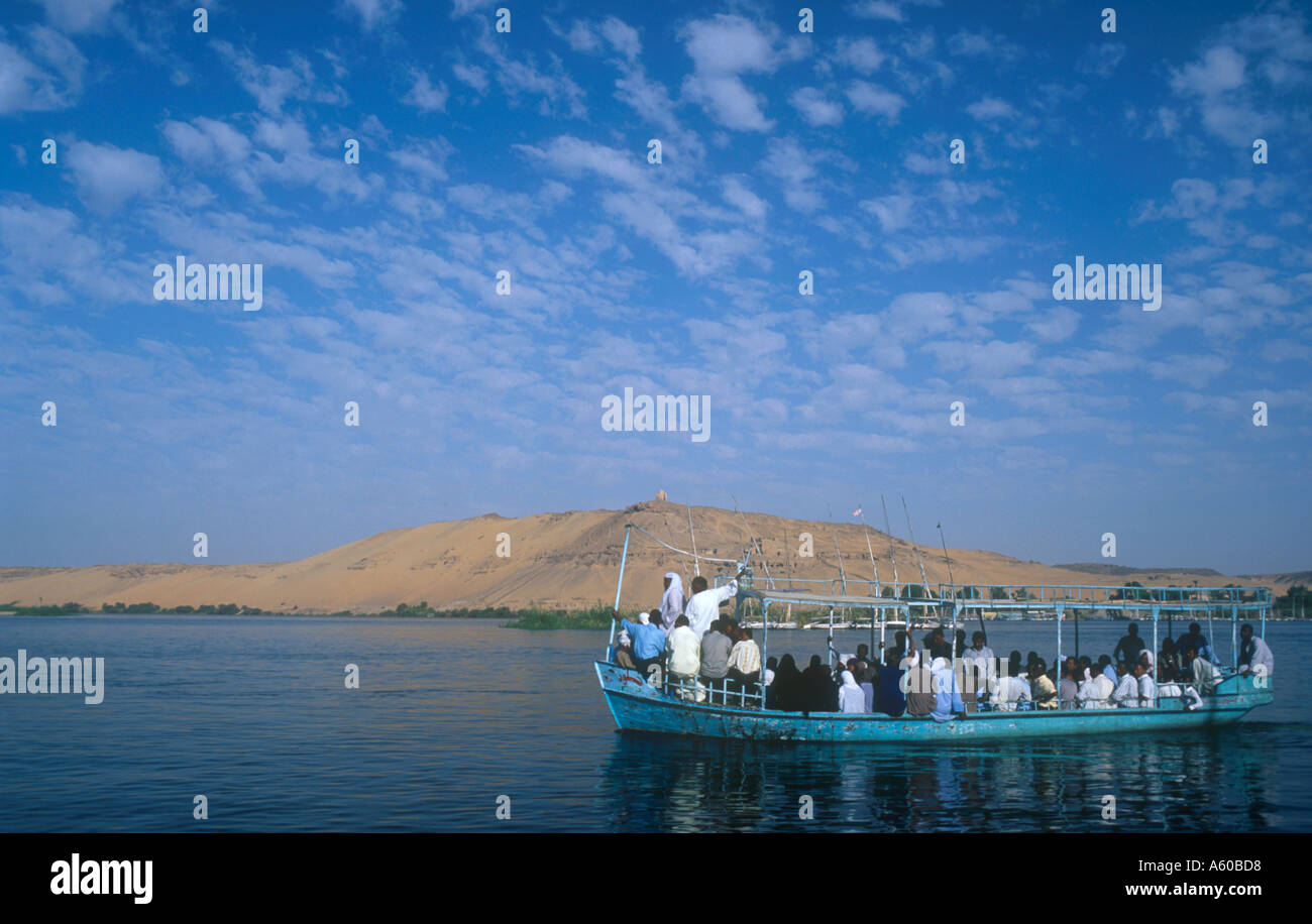 EGYPT Upper Egypt Aswan Qubbet el Hawa and The Tombs of The Nobles with a loaded passenger ferry sailing past on the river Nile - Stock Image