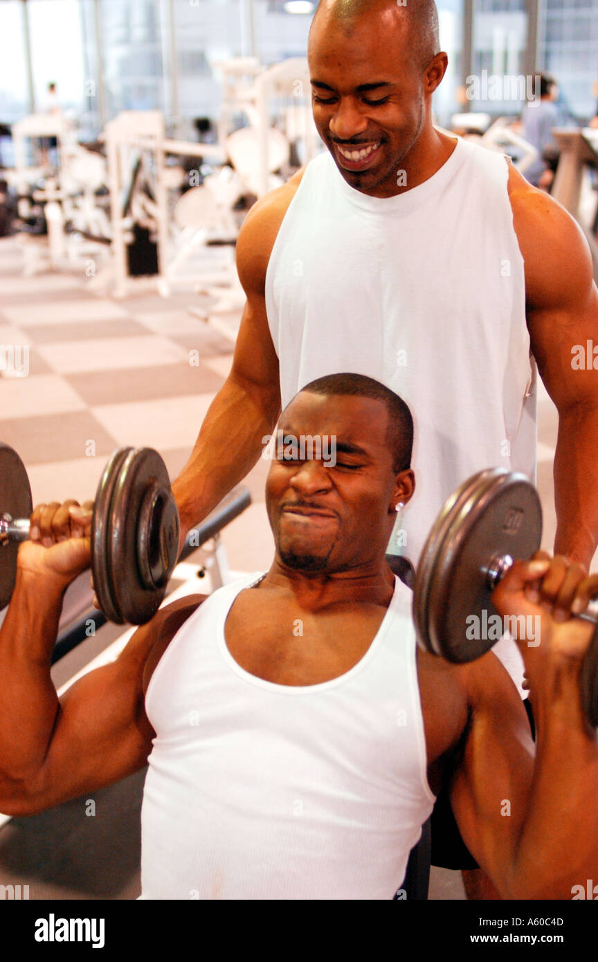 Two young black men lifting weights in a gym