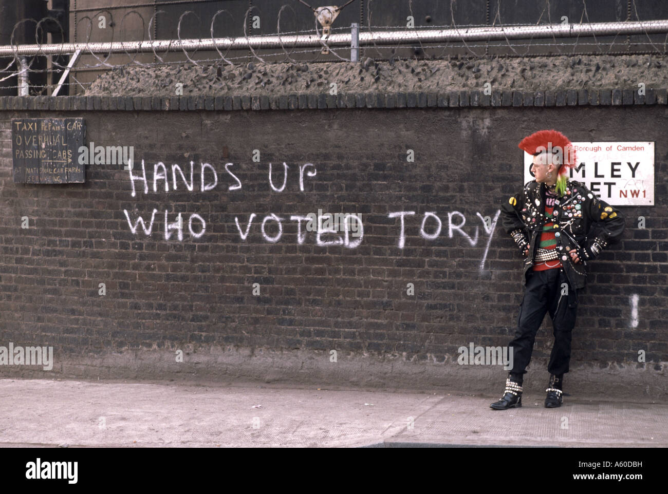 Punk standing in front of wall with graffiti saying hands up who voted Tory - Stock Image