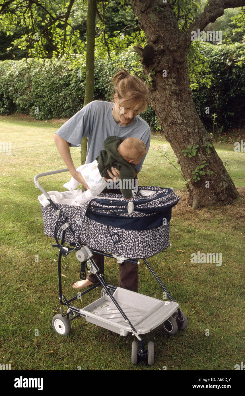 Mother placing four week old baby into stroller - Stock Image