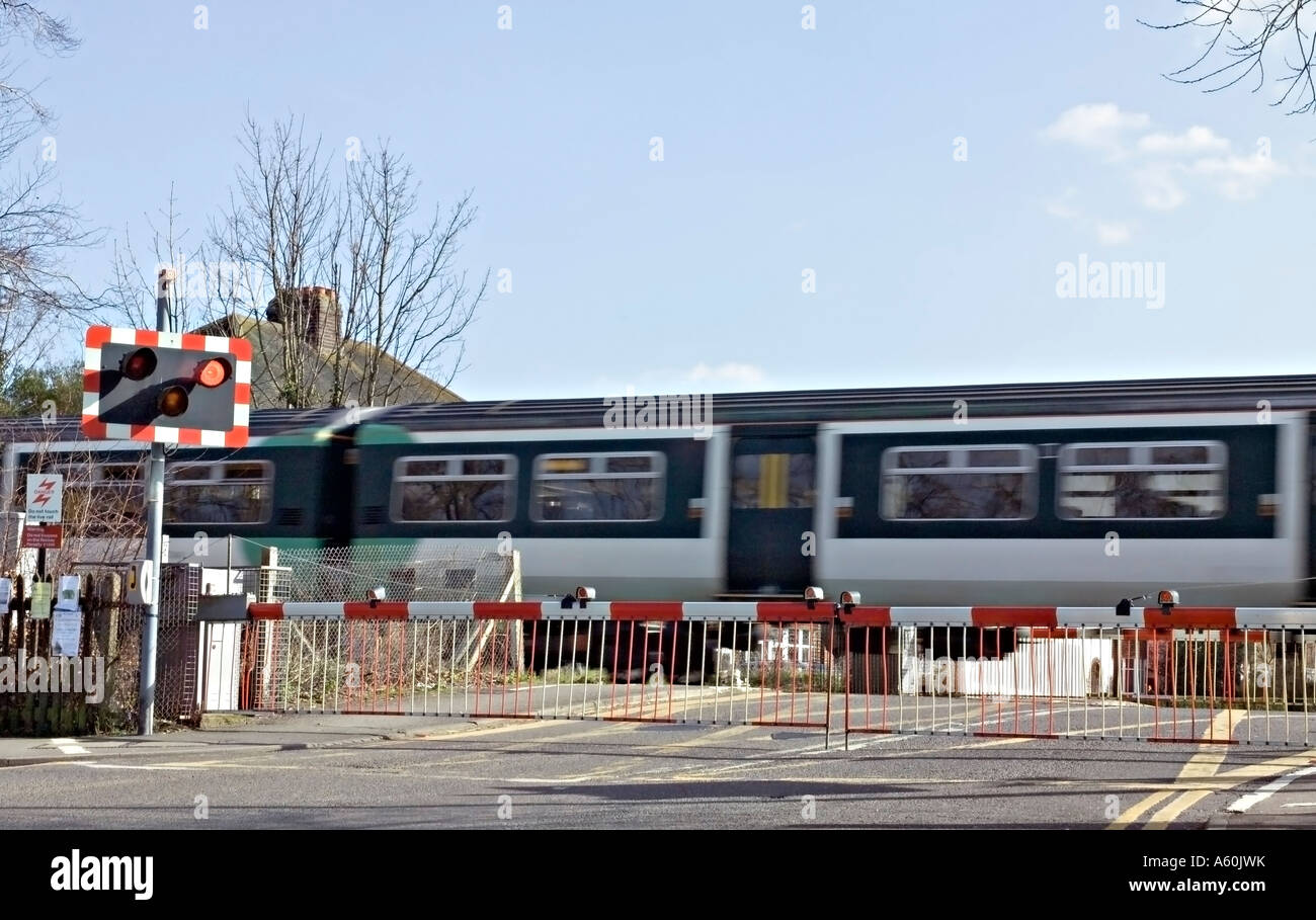 A train passing over a road crossing in Surrey, UK. Stock Photo