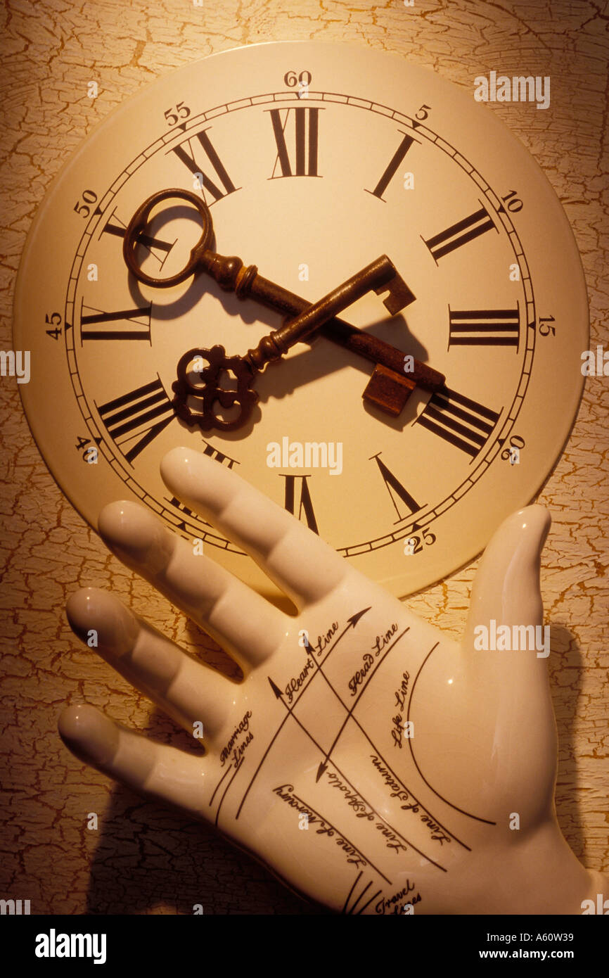 Two old skeleton keys on old clock face with fortune telling hand - Stock Image