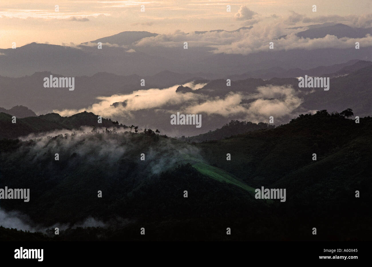 Sunset rainclouds and mist hover abouve the hills Trekking out of Kalaw Shan State Burma - Stock Image