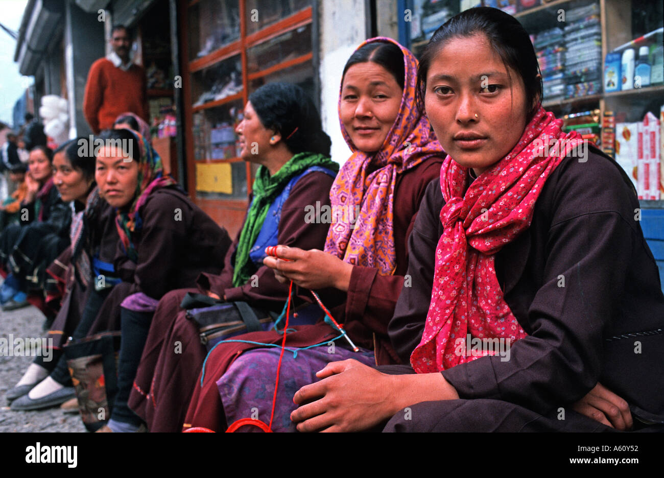 A row of friendly seated women at Keylong Himachal Pradesh foothills of the Himalayas waiting for transport Stock Photo