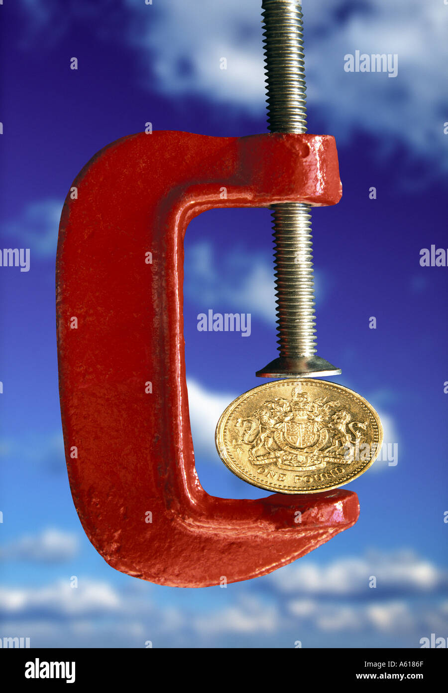 UK Pound squeezed in clamp - Stock Image