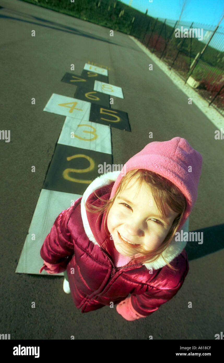 A young child playing hopscotch in a childrens playground Stock Photo