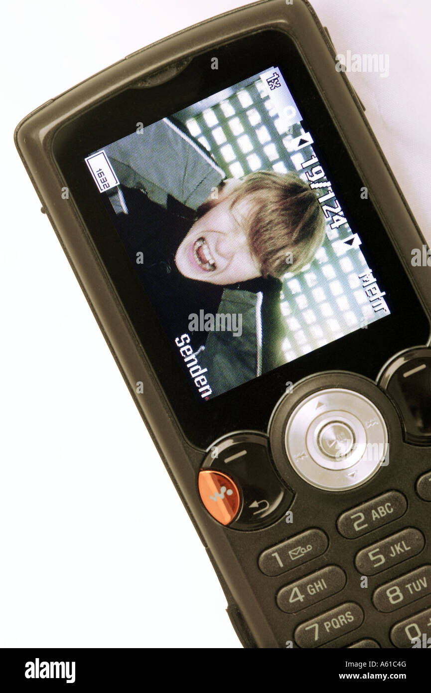 Boy cries and holds his ears, mobile phone display - Stock Image