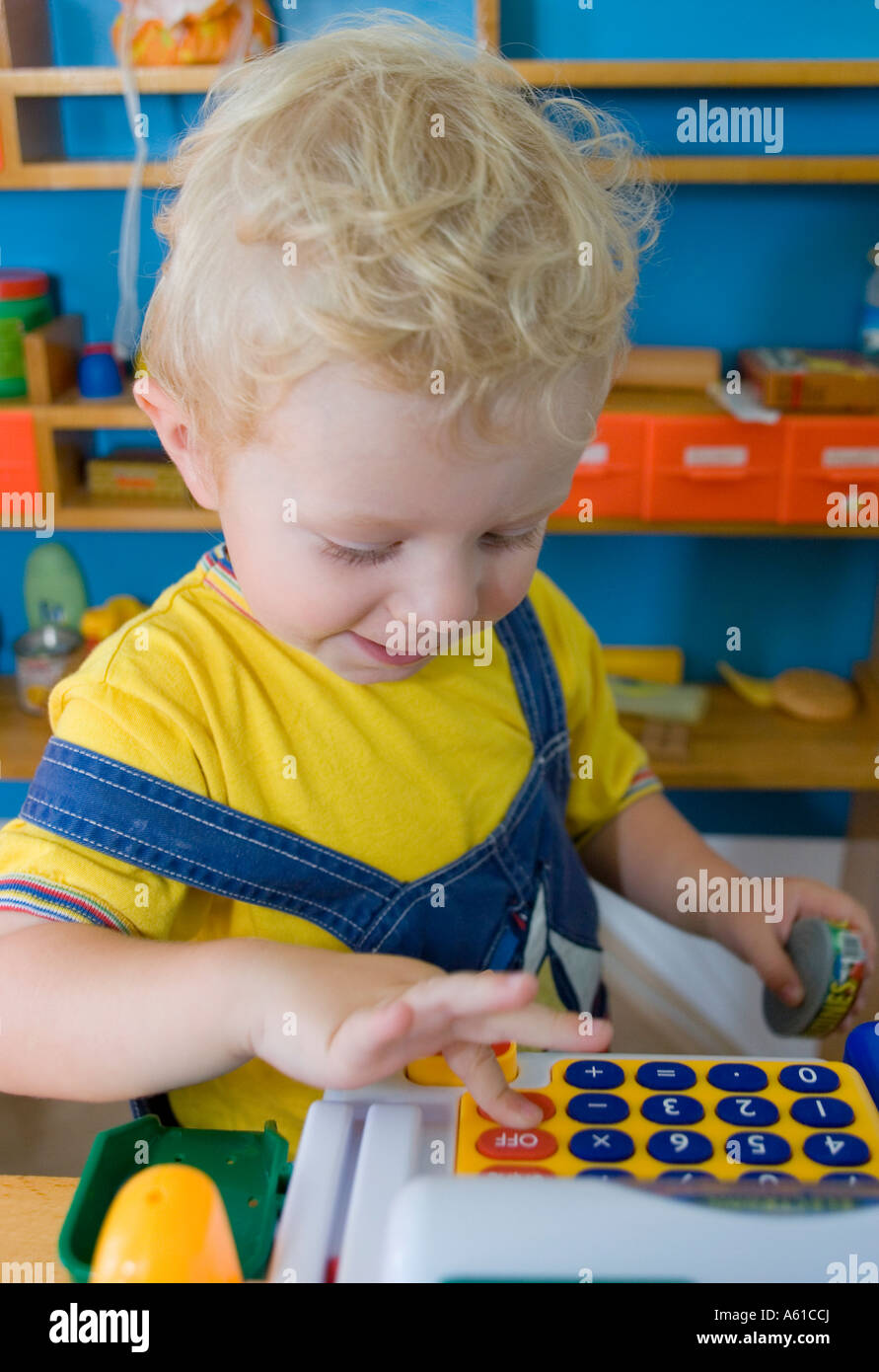 A two year old boy is playing with his till - Stock Image