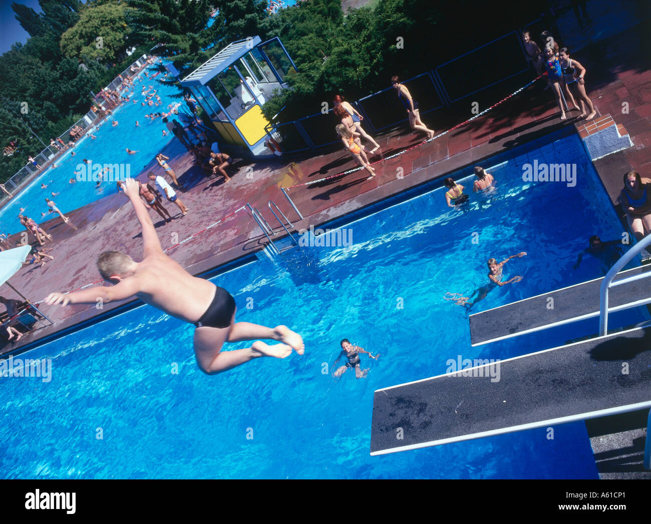 Rear view of boy jumping from diving board in swimming pool Stock ...