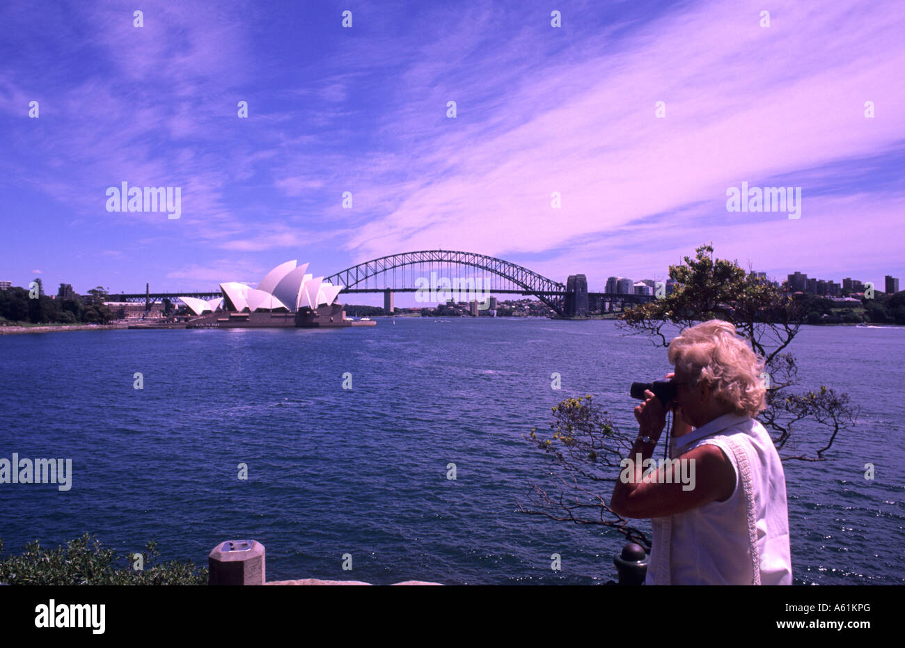 Woman tourist taking photograph of the famous Harbour Bridge and Opera House in Sydney Australia - Stock Image
