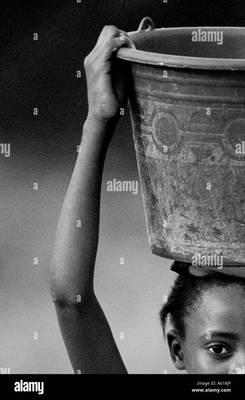 Young african girl carrying a bucket of water on her head, Ghana West Africa - Stock Image