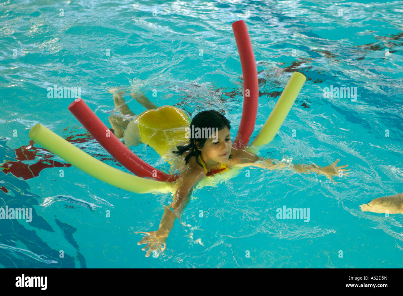 little girl learning to swim at an indoor swimming pool Stock Photo
