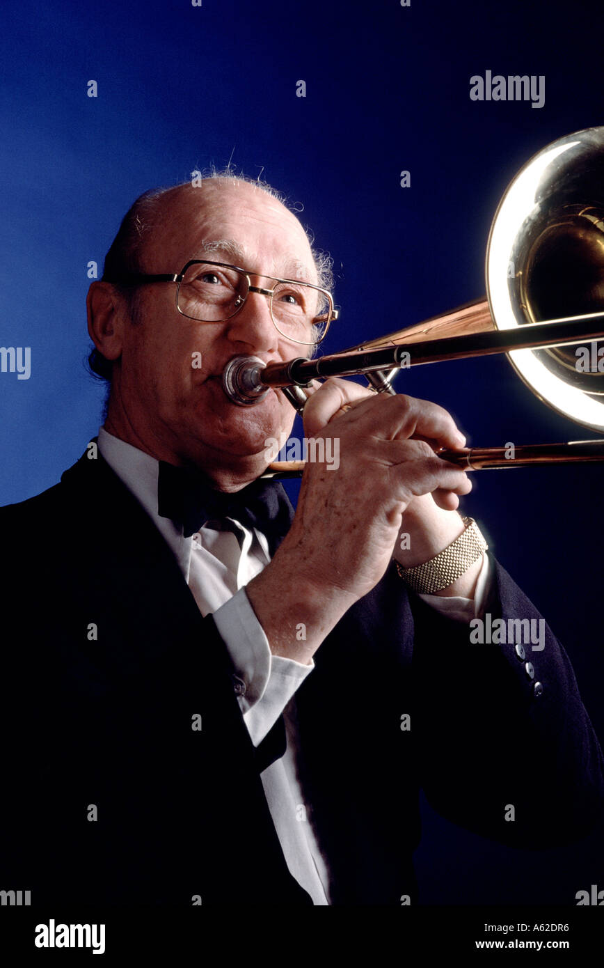 Studio shot of a musician playing a trombone - Stock Image