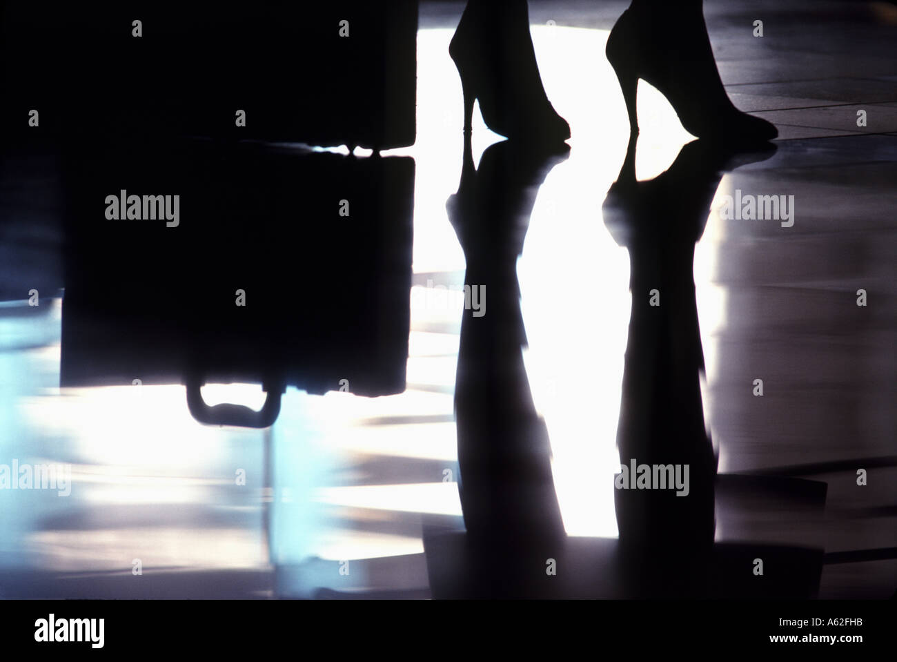 A graphic abstract of a woman's pair of high heels reflecting on a hotel lobby floor - Stock Image