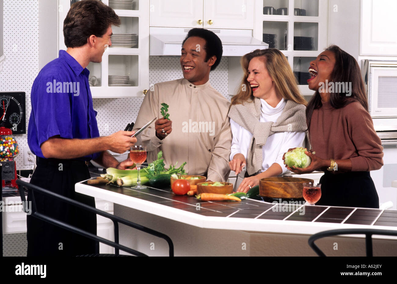 Black and white couples dating and relaxing at home cooking in kitchen - Stock Image