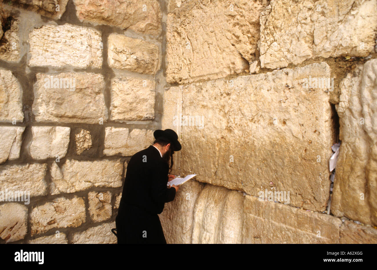 Religious worshipers practicing their religion and chanting and reading at the famous Western Wailing Wall in Jerusalem - Stock Image
