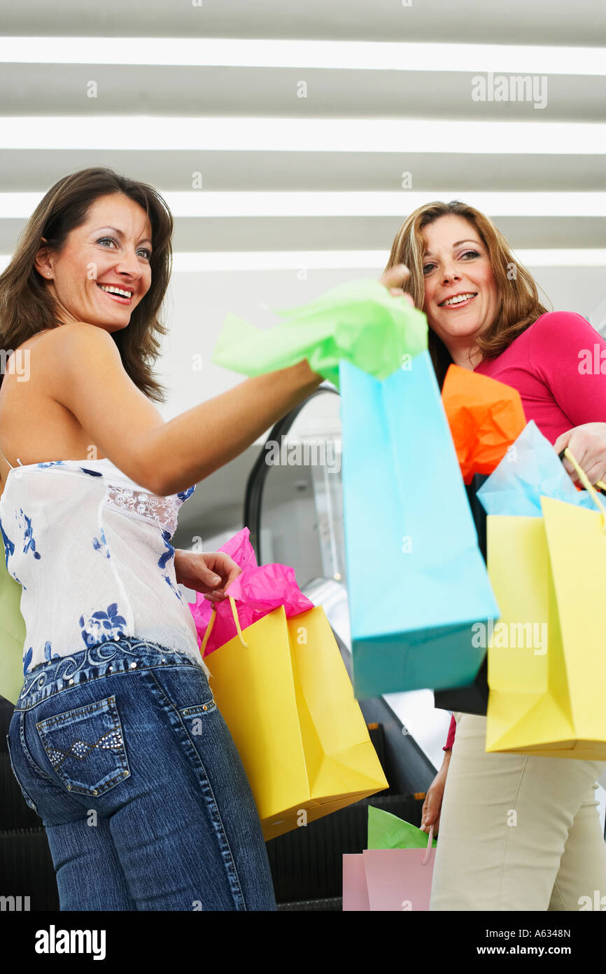 Side profile of a mid adult woman and a mature woman holding shopping bag on an escalator - Stock Image