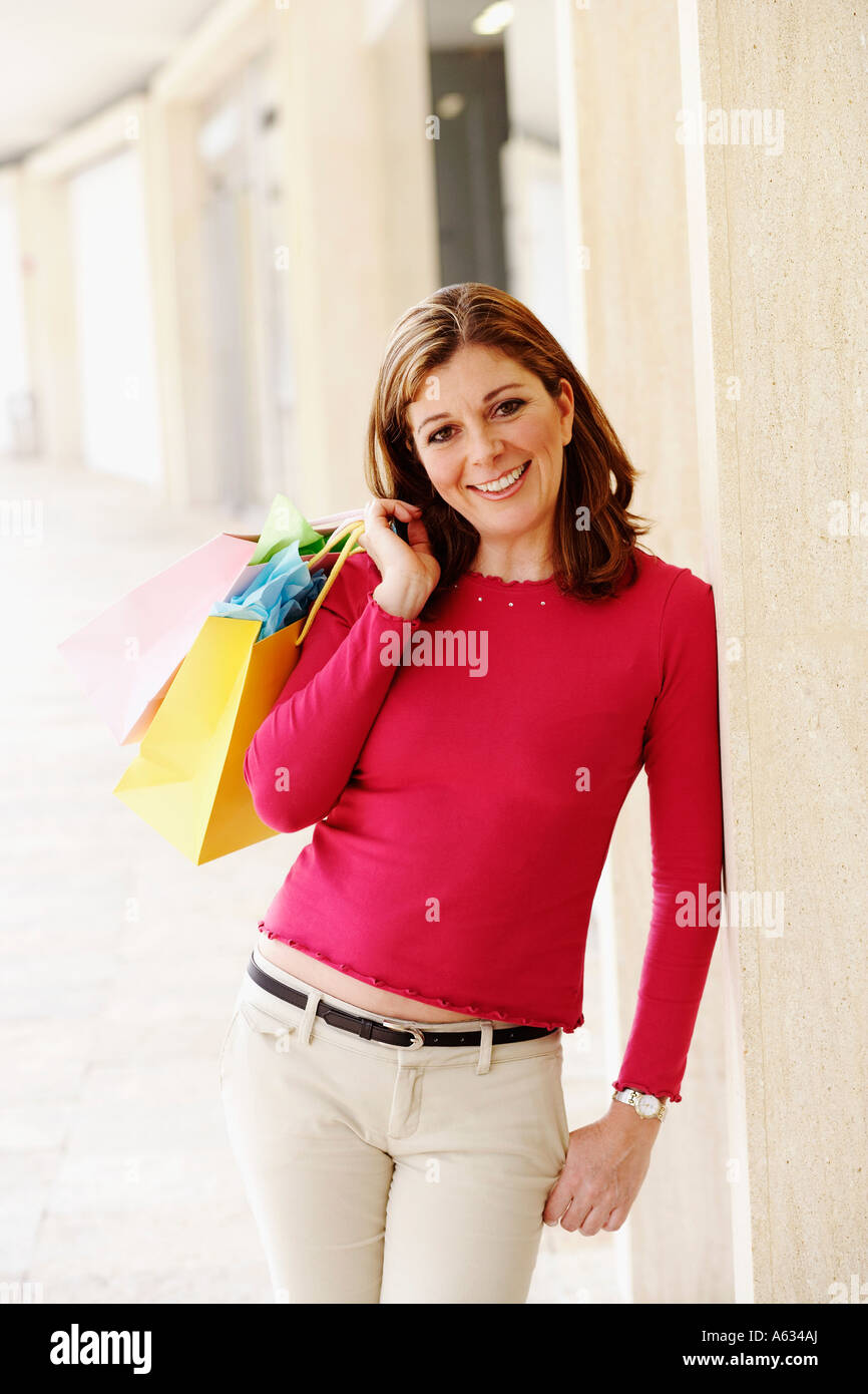 Portrait of a mature woman holding a shopping bag and smiling - Stock Image