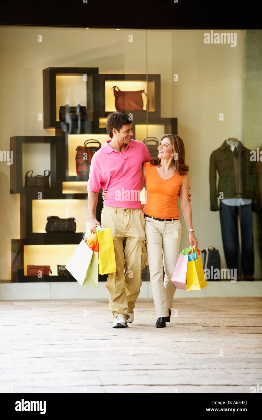 Mid adult man and a mature woman carrying shopping bags - Stock Image