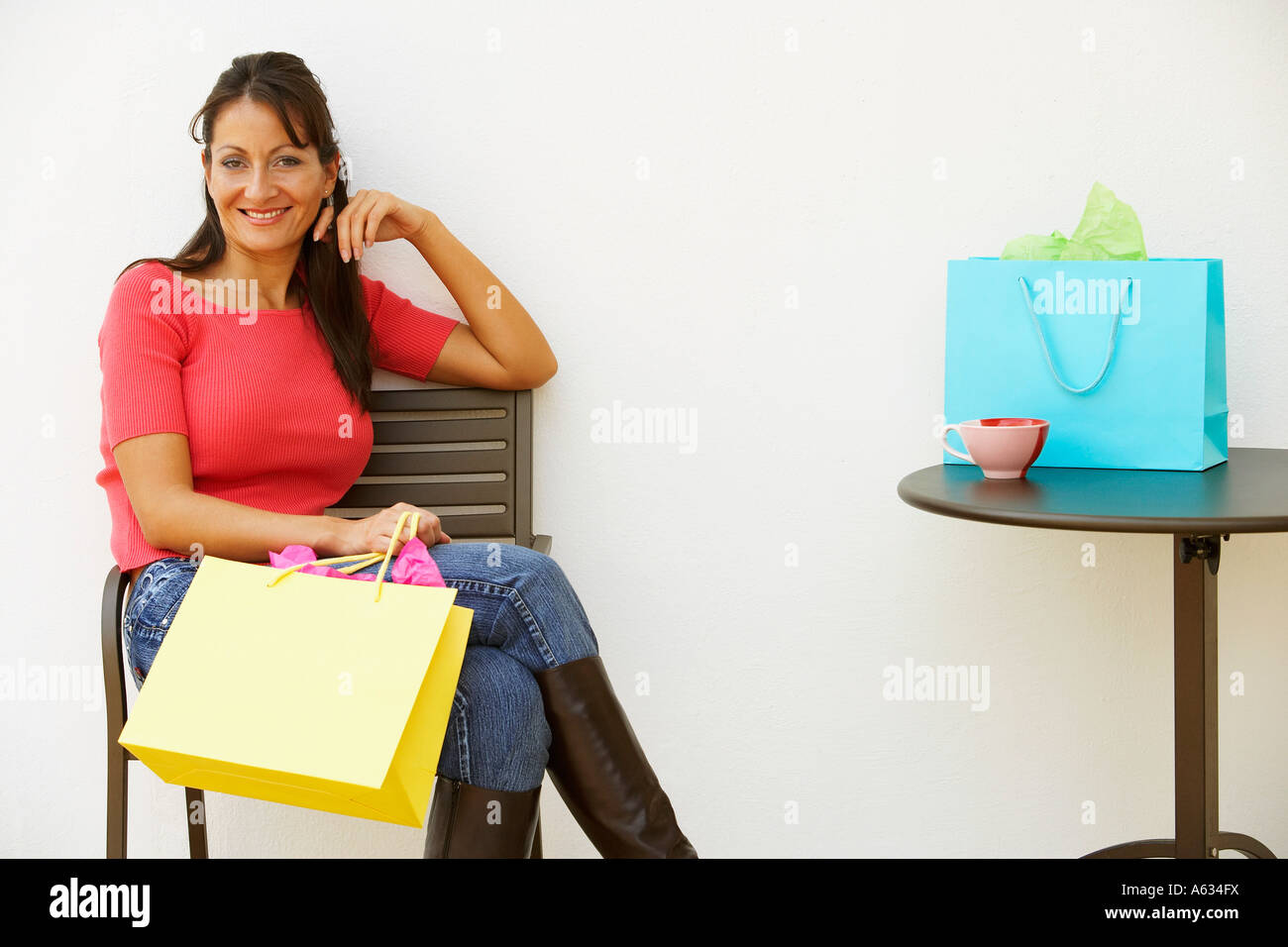 Portrait of a mid adult woman sitting in an armchair and smiling - Stock Image