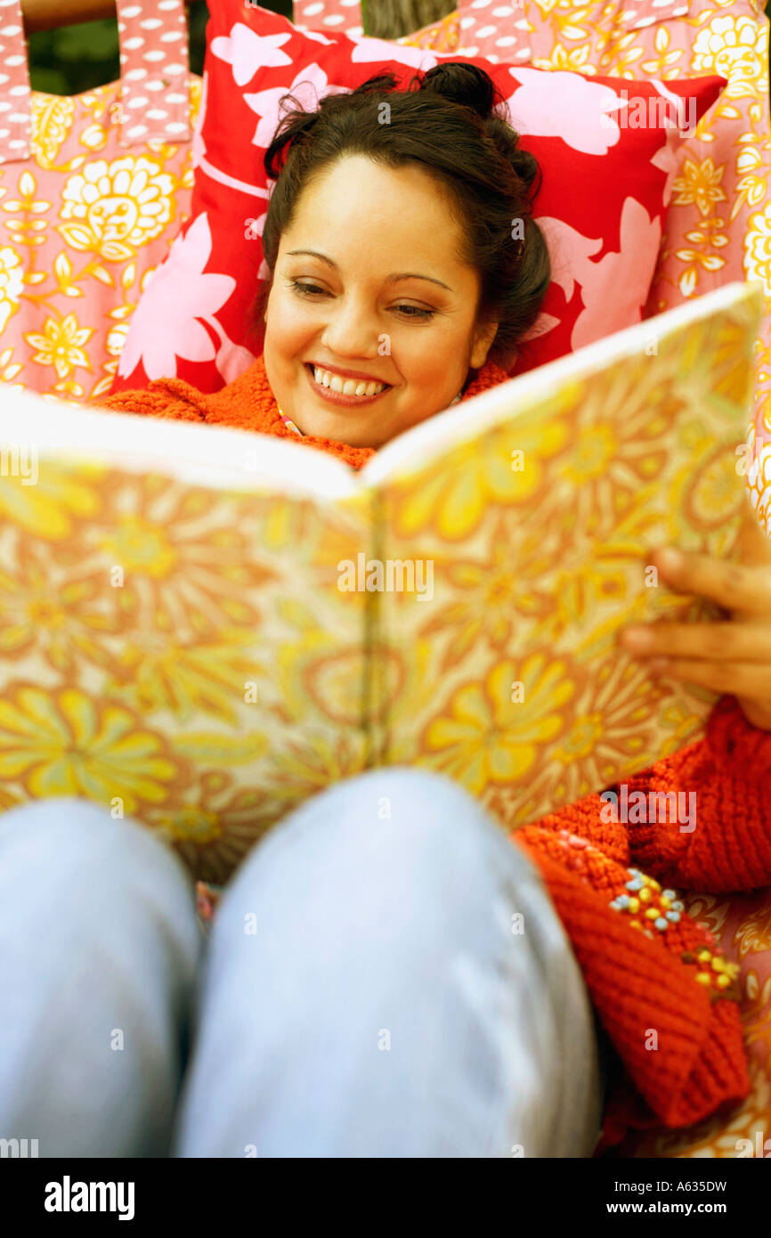 High angle view of a mid adult woman holding a photo album and lying in a hammock - Stock Image