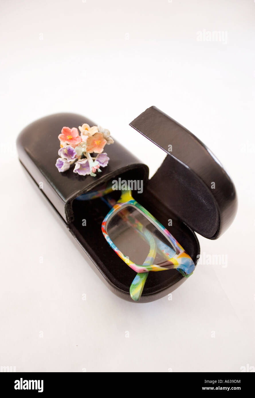 Funky eyeglasses in a coffin case.  Conceptual: Disposing of eyeglasses.  Caption space at the top. - Stock Image