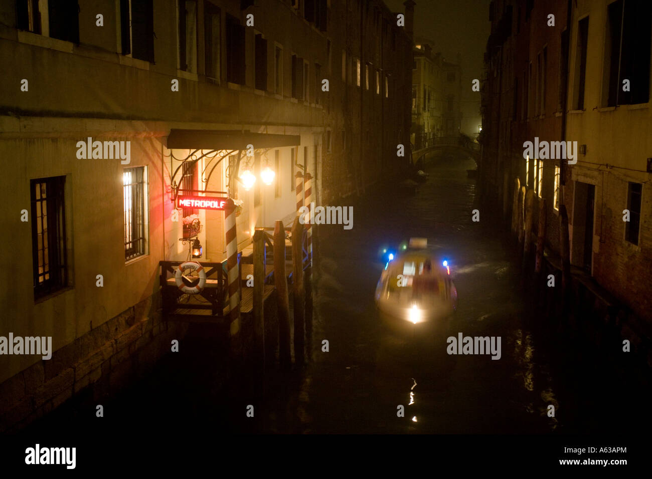 A police boat blue lights flashing travels along a canal past the Metropole Hotel on a foggy night in Venice - Stock Image