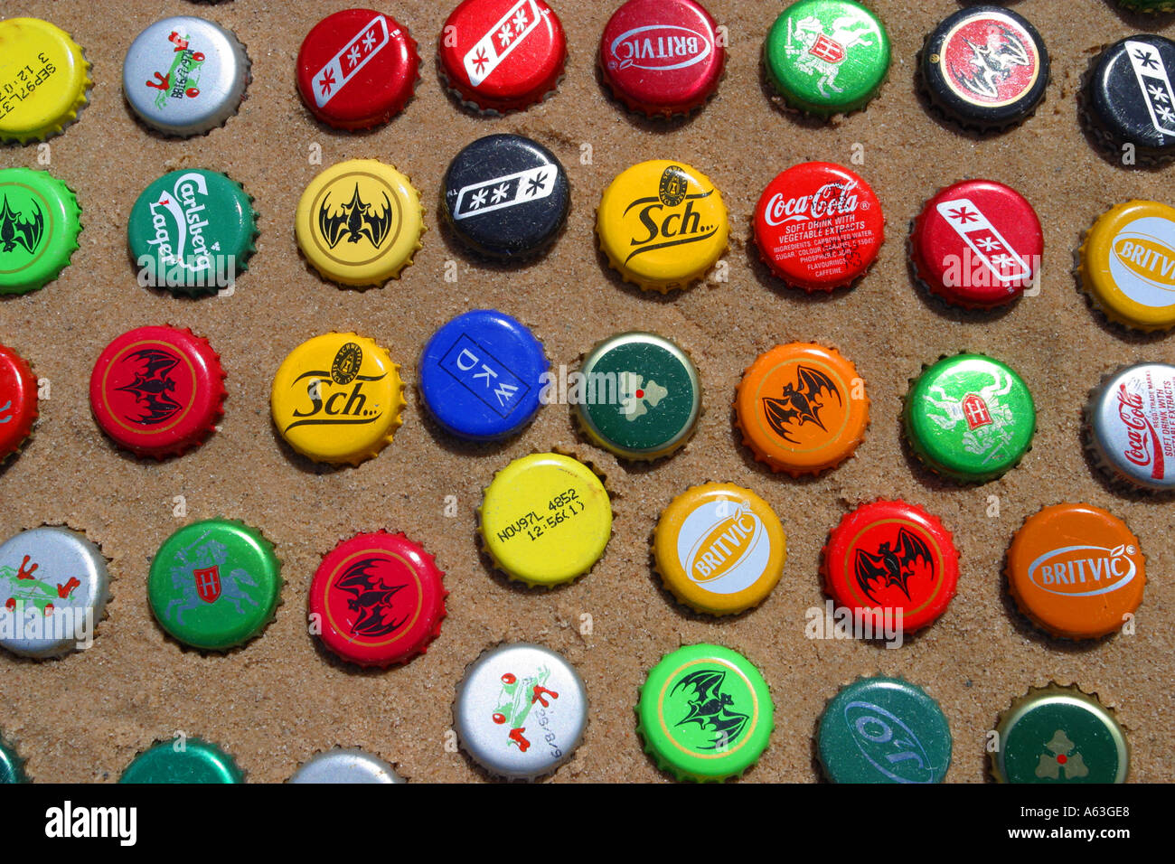 Multi coloured beer bottle tops displayed on sand as beach art - Stock Image