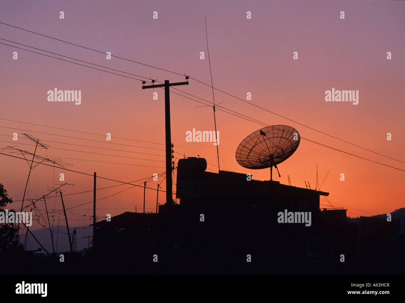 tv satellite dish, tv aerials, telephone wires and telegraph pole at  sunset, near uruapan, mexico