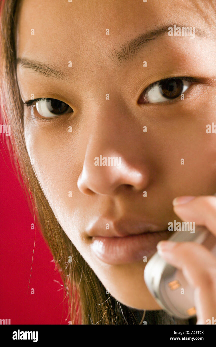 Asian woman using cell phone - Stock Image