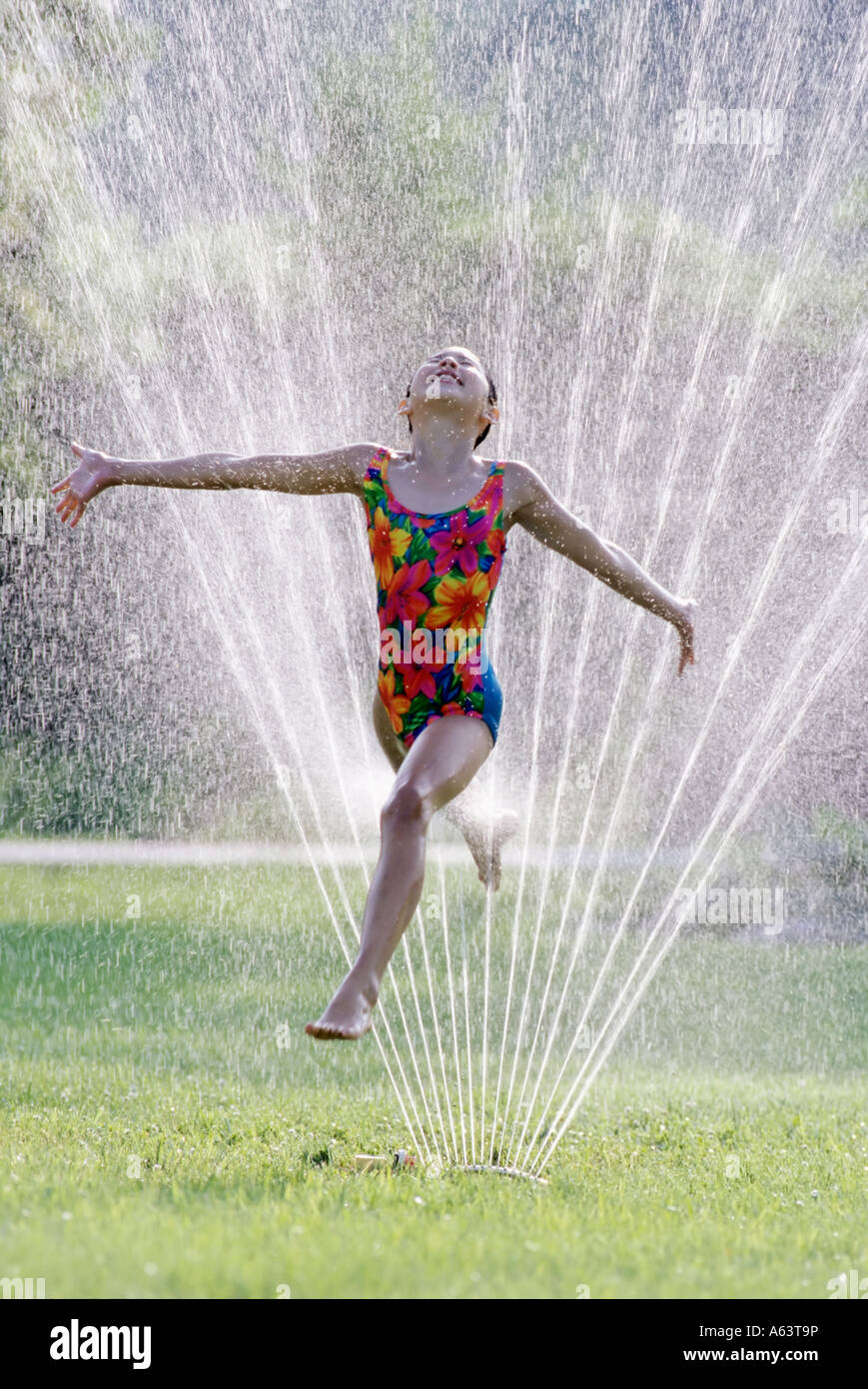 Girl running through sprinkler in a park - Stock Image
