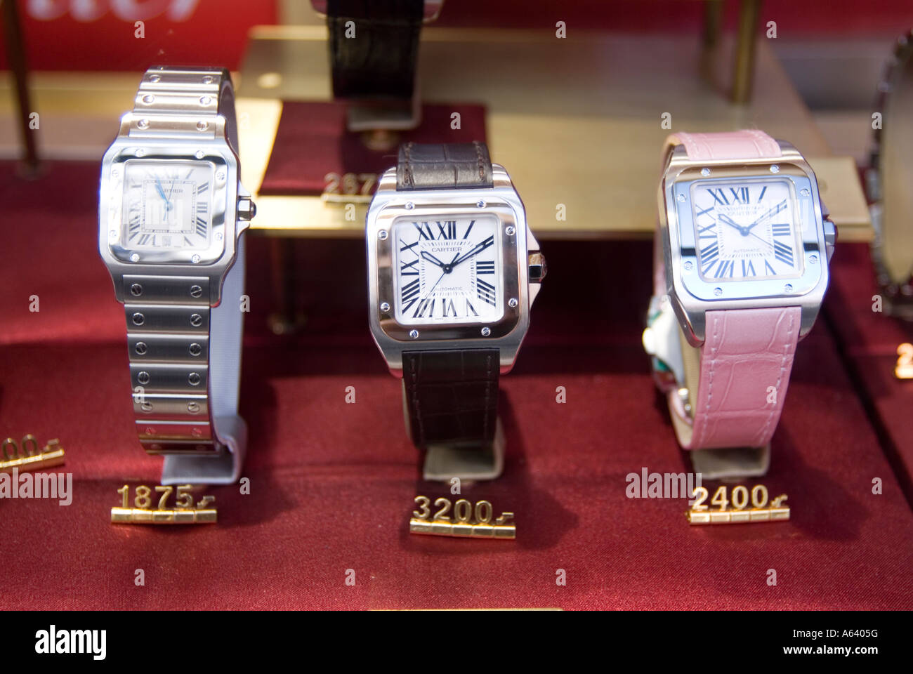 Expensive Cartier watches in shop window display London England UK - Stock Image