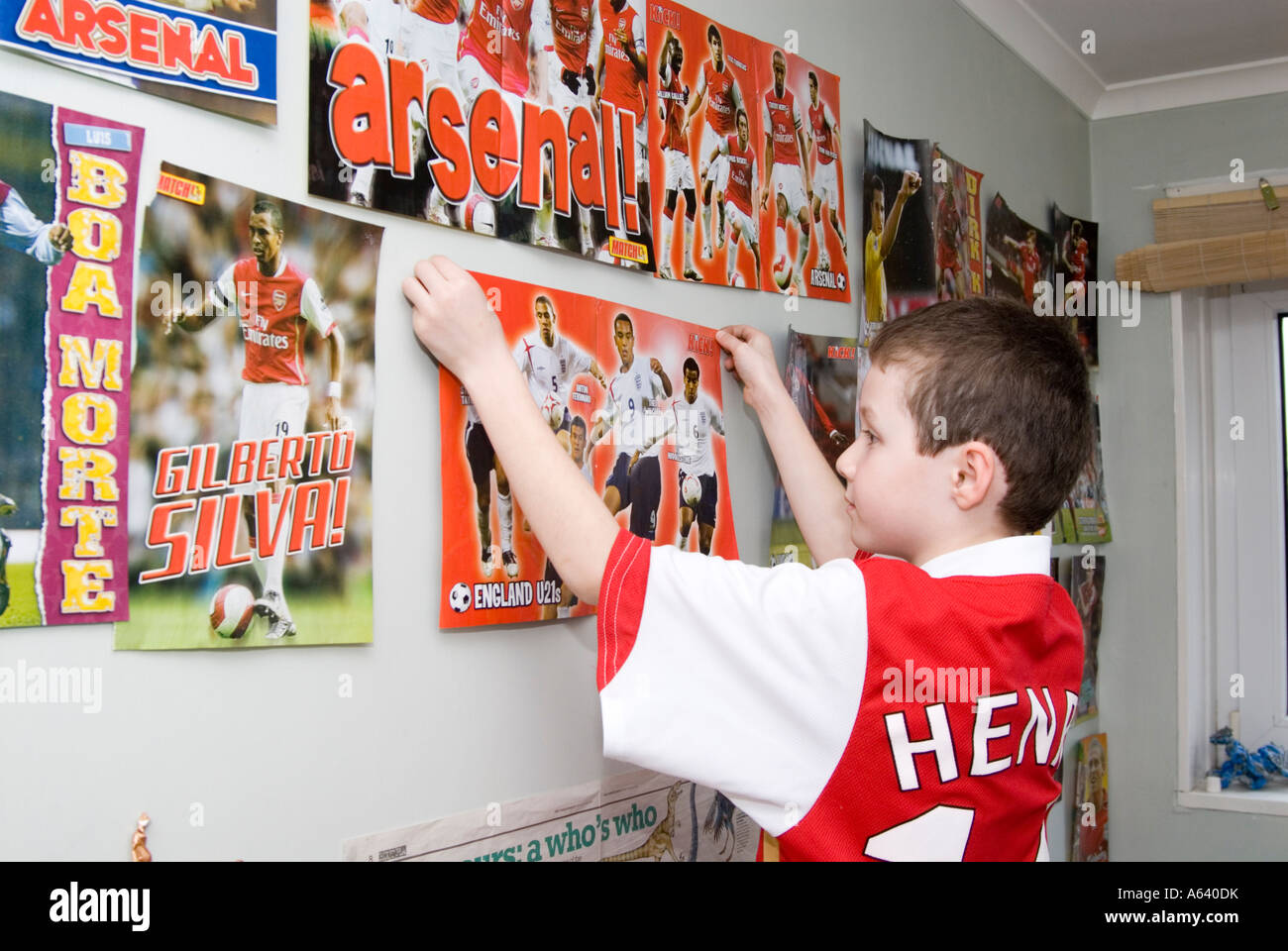 Young Arsenal football supporter boy putting up posters on his bedroom wall, London, England, UK - Stock Image