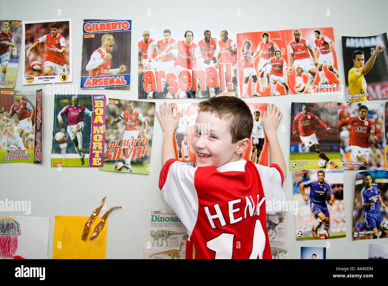 wall posters for bedroom. Young Arsenal football supporter boy putting up posters on his bedroom wall  London England UK Stock