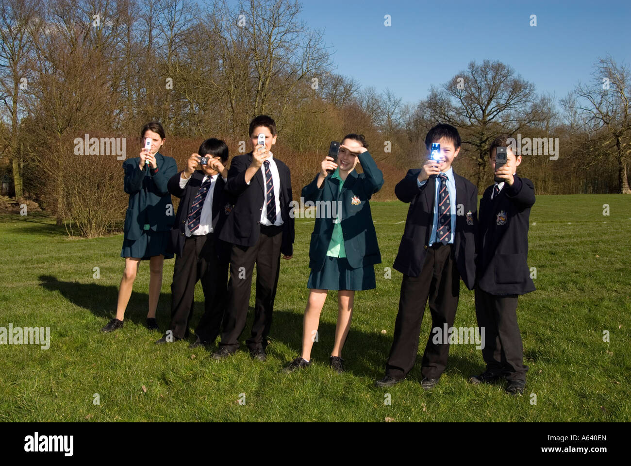 Group of school children in uniform taking photos with their mobile phones, England UK - Stock Image