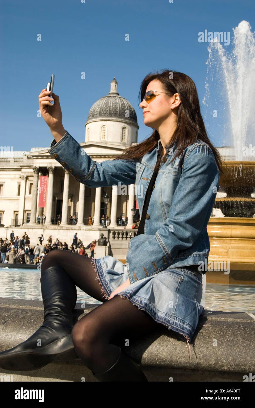 Beautiful young woman tourist taking photos with mobile phone camera at Trafalgar Square London England UK - Stock Image