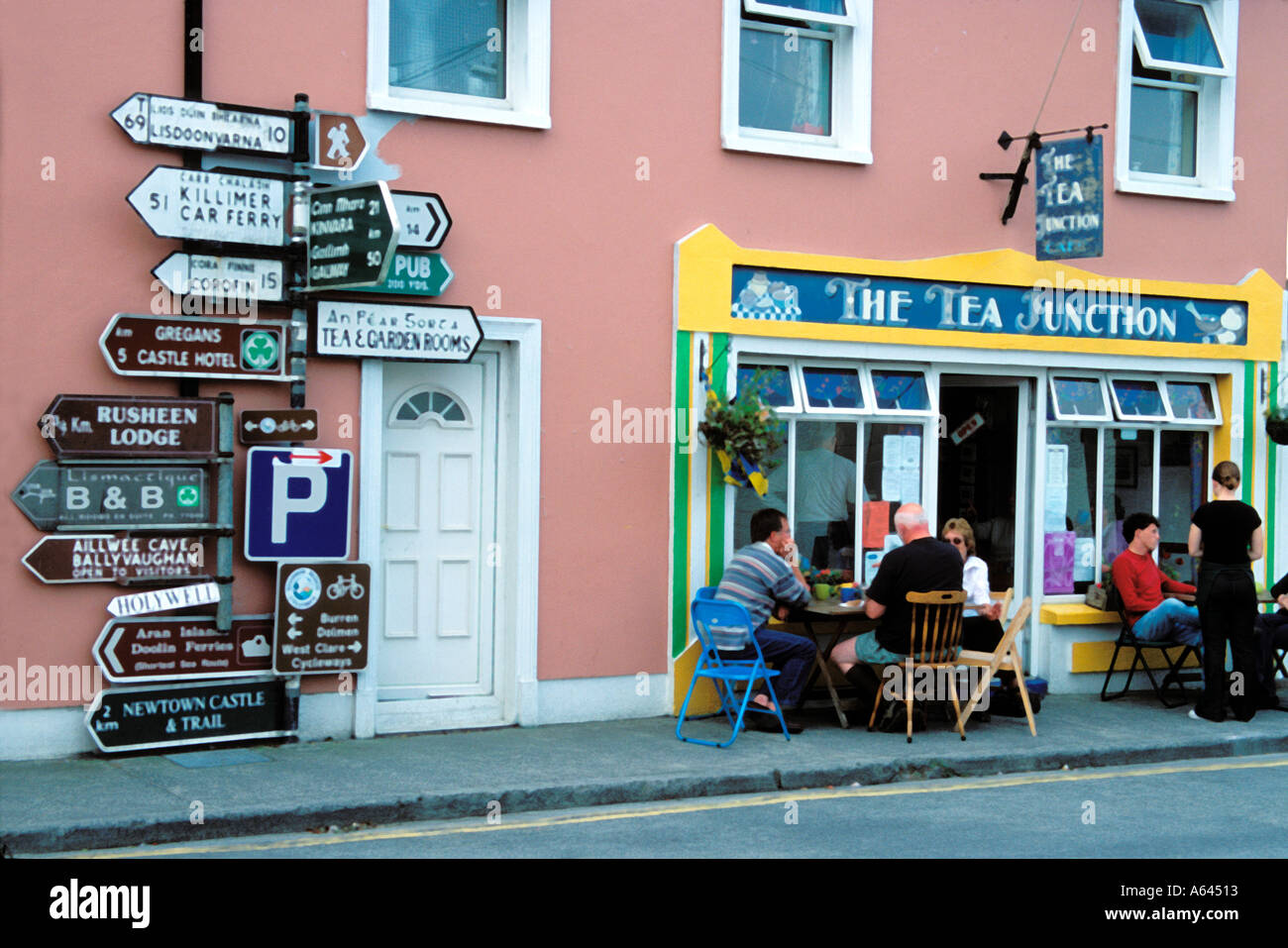 A busy signpost next to a quiet tea cafe in Ballyvaughan County Clare Republic of Ireland - Stock Image