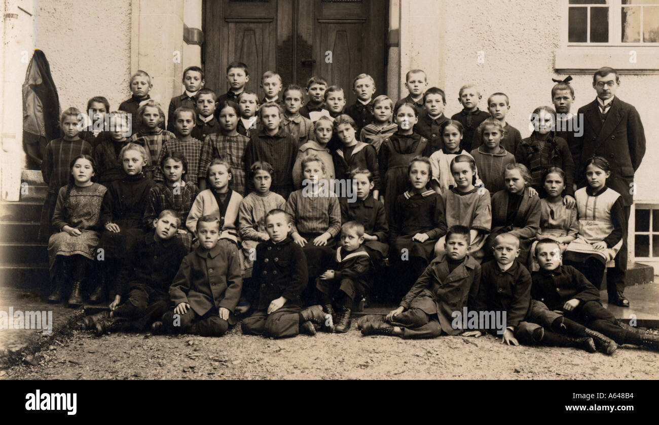 Historical picture schoolclass in the year 1900 boys and girls with teacher infront of the school - Stock Image