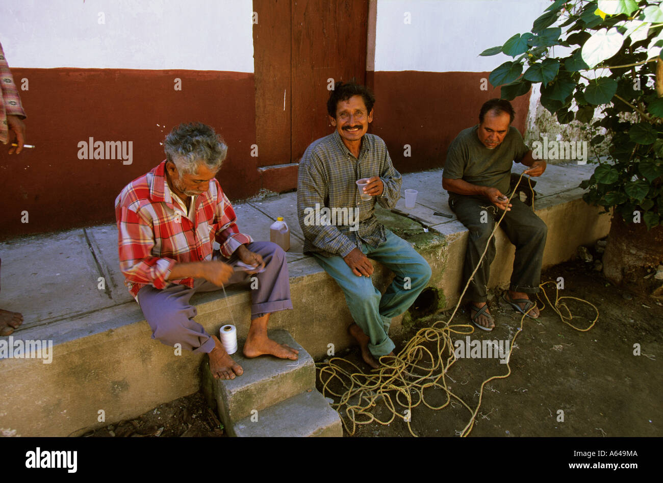 Mexico Nayarit Mexcaltitan fishermen patching nets - Stock Image