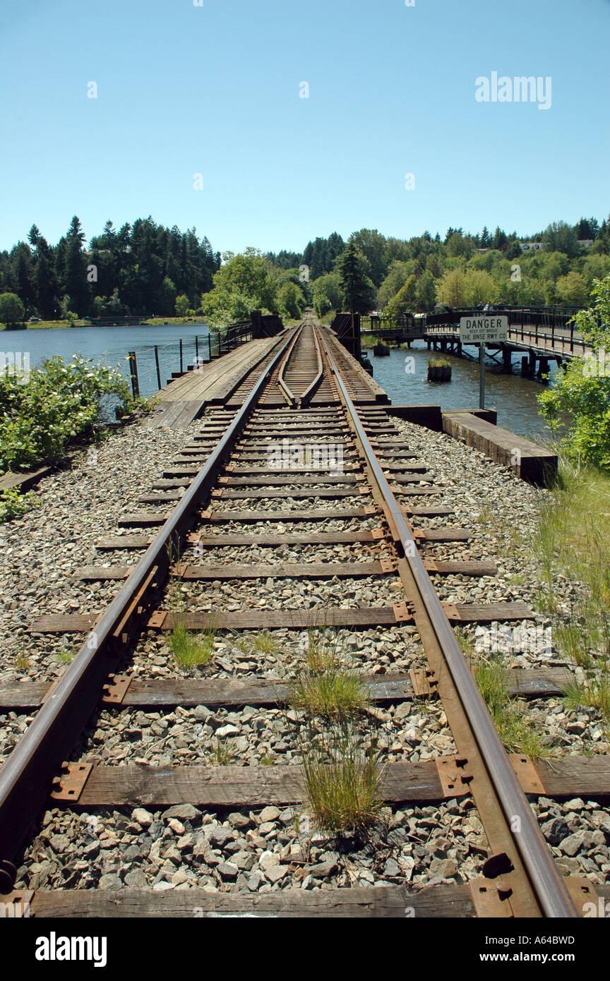 Railroad tracks go over trestle into distance - Stock Image