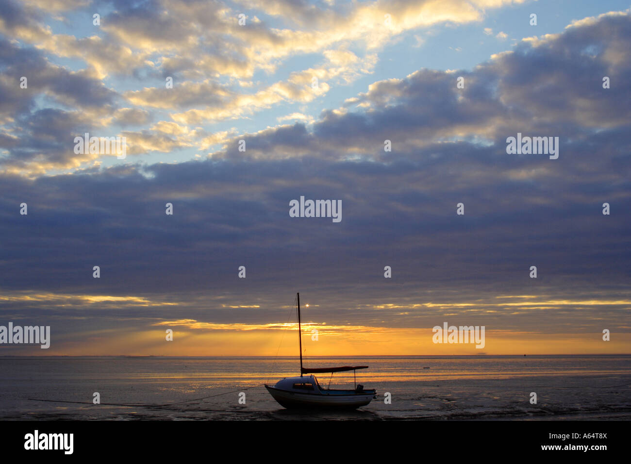 Solitary boat in the sea at Snettisham beach, West Norfolk coast with glorious sunset behind - Stock Image